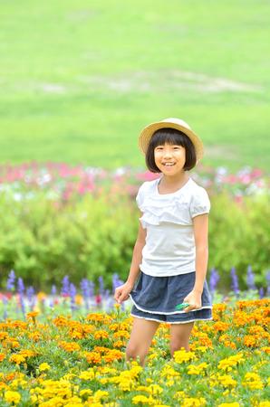 Girls smiling in the flower garden (straw hat