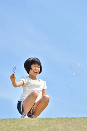 Girls playing with soap bubbles in the blue sky
