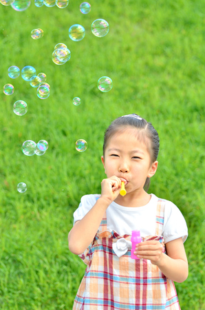 Girls playing with soap bubbles in the grassland