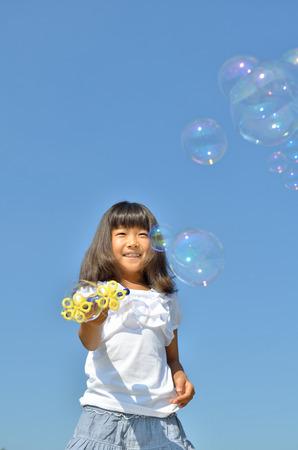 푸른 하늘에 비누 거품을 가지고 노는 소녀