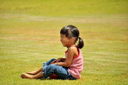 Girls sit down in the grassland Stock Photo