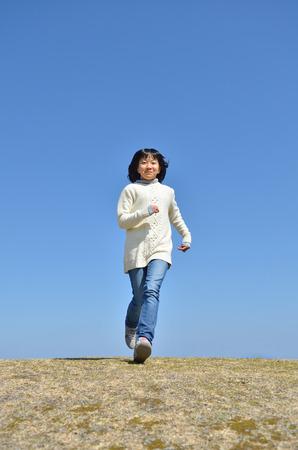 Girls running in the blue sky Stock Photo