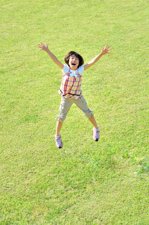 Girls jumping in the grass land Stock Photo