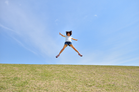 Girls jumping in the blue sky Stock Photo