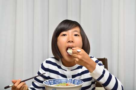 Girl's eating chinese noodle 스톡 콘텐츠