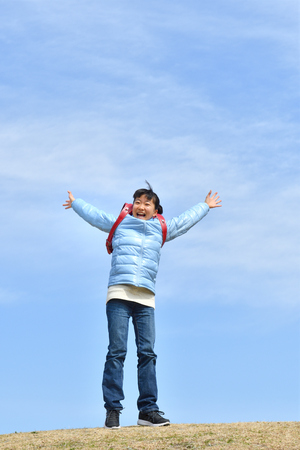 Japanese elementary school girl raising her both hands in the blue sky