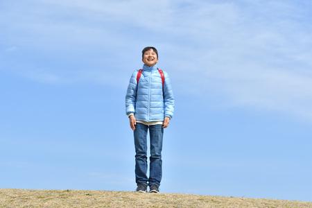Japanese elementary school girl smiling in the blue sky