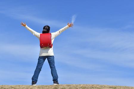 Japanese elementary school girl deep breathing in the blue sky (rear view) Stock Photo