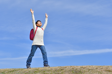 Japanese elementary school girl raising hands in the blue sky Фото со стока