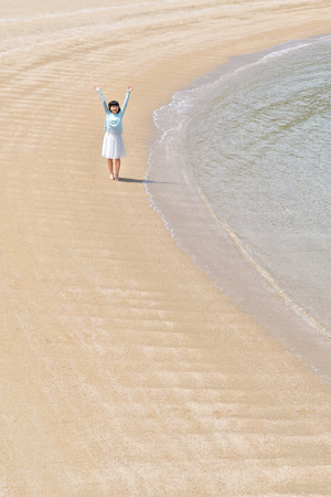 Japanese girl raising hands in the beach 免版税图像