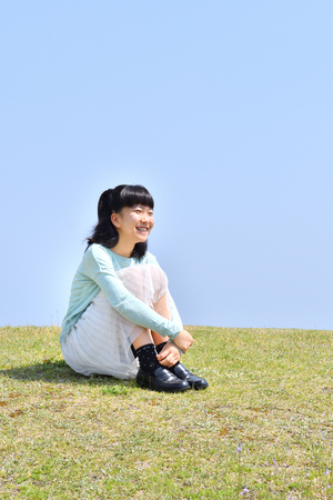 Japanese girl sitting down on the grassland