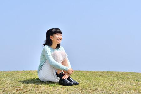 Japanese girl sitting down on the grassland