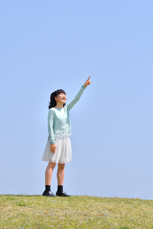 Japanese girl pointing at the blue sky