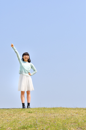 Japanese girl striking a victory pose in the blue sky