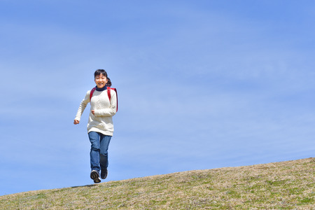 Japanese elementary school girl running in the blue sky