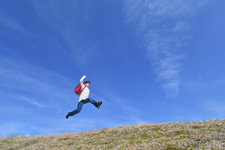 Japanese elementary school girl jumping in the blue sky