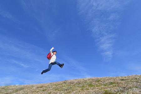 Japanisches Grundschulmädchen, das in den blauen Himmel springt