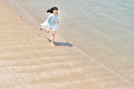 Japanese girl running in the beach 免版税图像