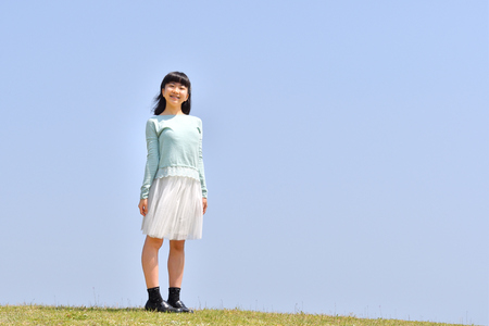 Japanese girl smiling in the blue sky Фото со стока