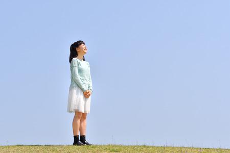 Chica japonesa mirando hacia arriba en el cielo azul