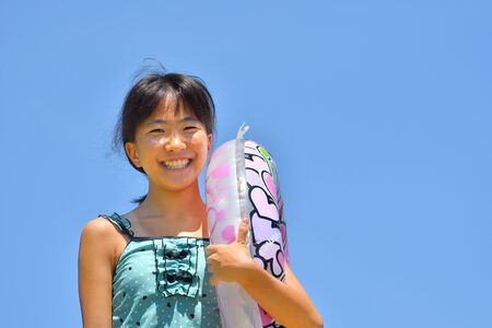 Japanese girl enjoys sea bathing - blue sky