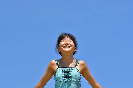 Japanese girl enjoys sea bathing - in the blue sky