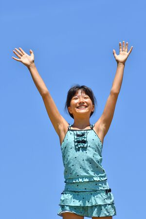Chica japonesa disfruta bañándose en el mar - en el cielo azul Foto de archivo