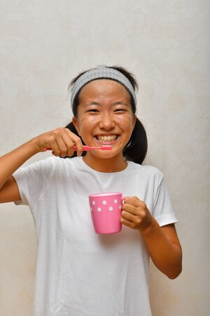 Japanese girl is brushing her teeth