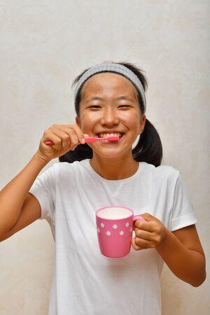Japanese girl is brushing her teeth Stock Photo