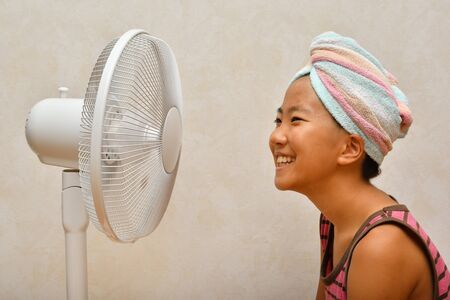 Japanese girl cools down after a bath by electric fan