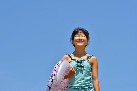 Japanese girl enjoys sea bathing - blue sky