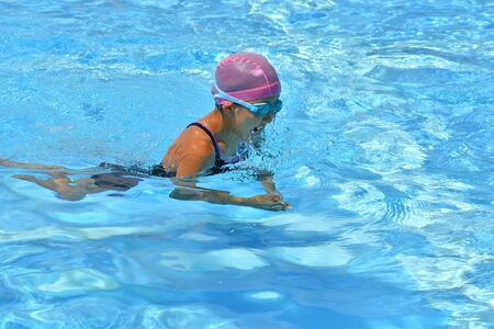 Japanese girl is swimming the breast stroke in the pool