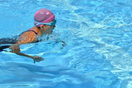 Japanese girl is swimming the breast stroke in the pool 스톡 콘텐츠 - 130422902