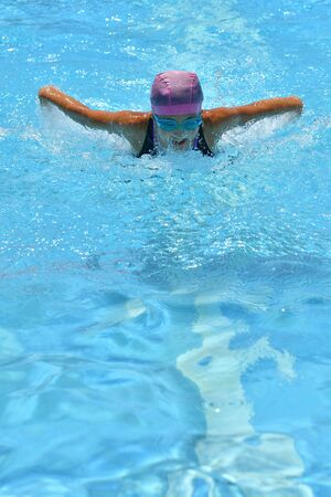 Japanese girl is swimming the butterfly stroke in the pool 版權商用圖片
