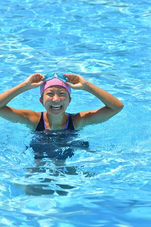 Japanese girl enjoys swimming in the pool