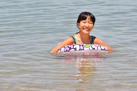 Japanese girl enjoys sea bathing - summer vacation