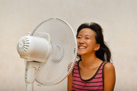 Japanese girl cools down by the electric fan after having a bath