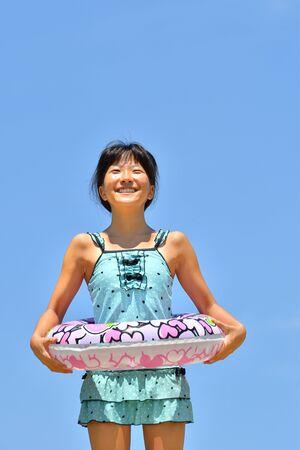Japanese girl enjoys sea bathing - blue sky 스톡 콘텐츠