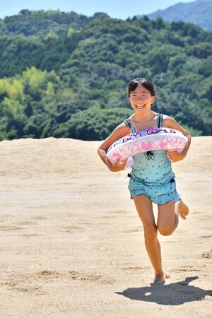 Japanese girl running in the beach