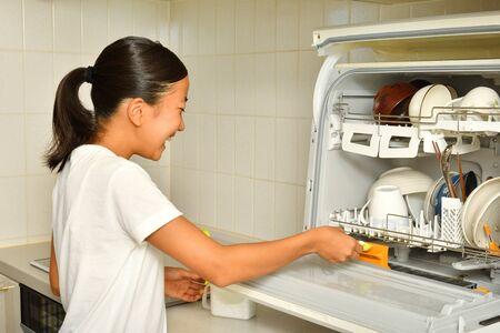 Chica japonesa hace el trabajo de la casa - Lavavajillas