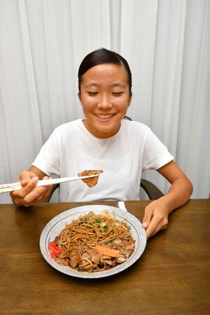 Japanese girl eating stir fried noodle with vegetable and meat 写真素材