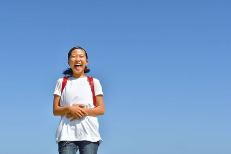 Japanese elementary school girl smiling in the blue sky