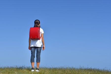 Japanese Elementary School Girl Standing in the Blue Sky (rear view)