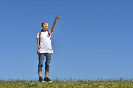 Japanese elementary school girl pointing in the blue sky 스톡 콘텐츠