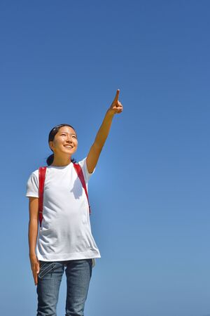 Japanese elementary school girl pointing in the blue sky