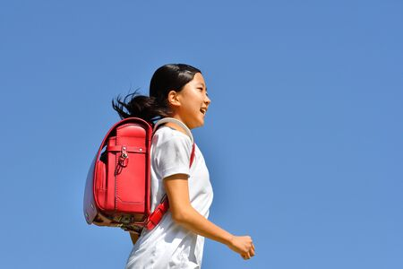 Japanese elementary school girl running in the blue sky