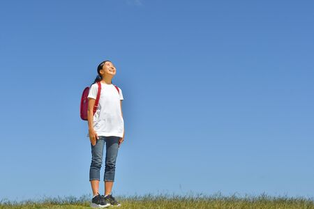 Japanese Elementary School Girl Looking up in the Blue Sky Фото со стока