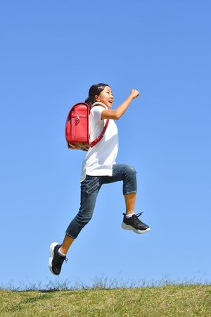Ragazza della scuola elementare giapponese che salta nel cielo blu Archivio Fotografico