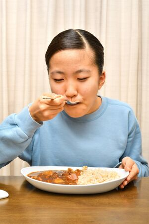 Japanese girl enjoys having curry and rice Stock Photo