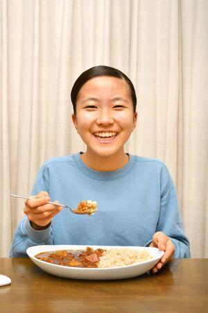 Japonesa disfruta de curry y arroz Foto de archivo